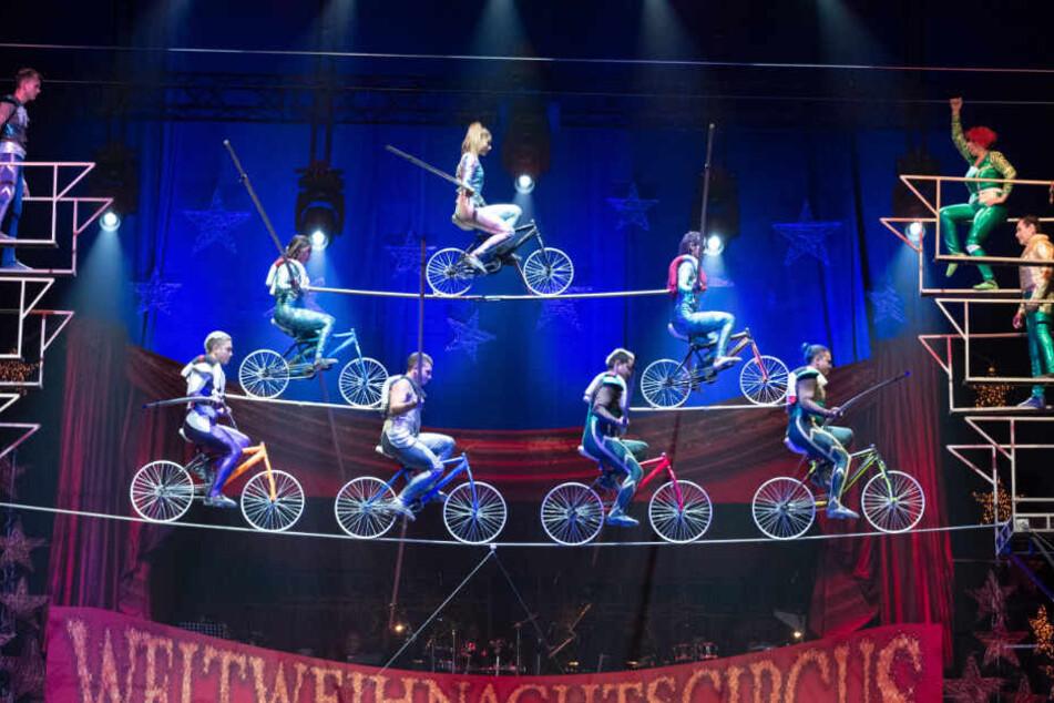 Die Artisten fahren mit Fahrrädern auf einem Hochseil.