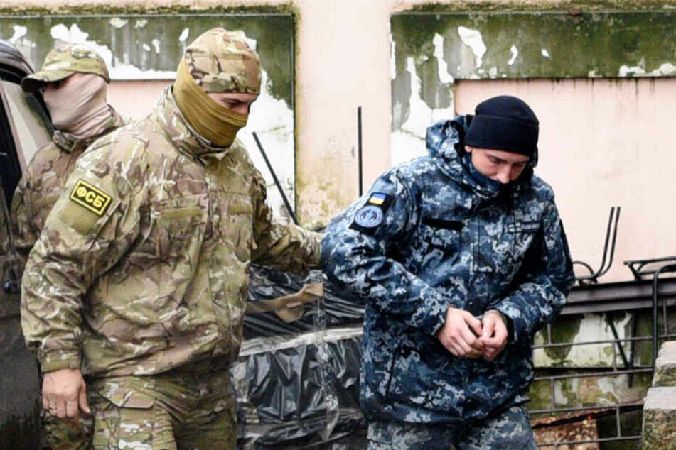 Ein russischer Soldat bringt den Gefangenen an einen unbekannten Ort.