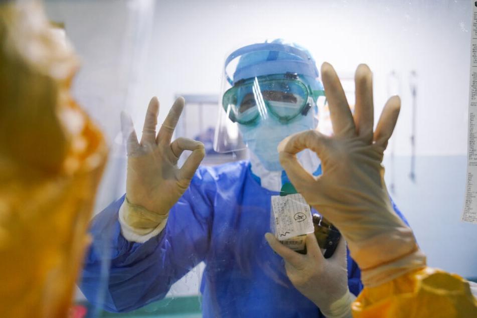 Zhangzhou: Mediziner gestikulieren durch das Fenster im Zhangzhou Municipal Hospital, in der südostchinesischen Provinz Fujian.