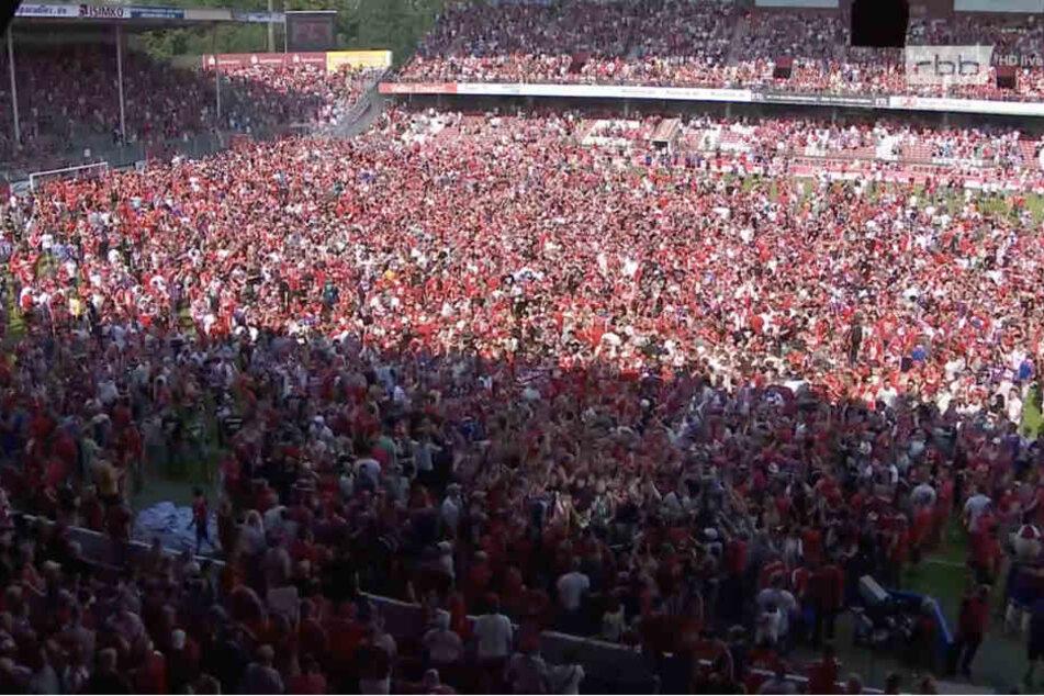 Nach Abpfiff stürmten die Fans den Platz und mittendrin das Fernsehteam des RBBs.