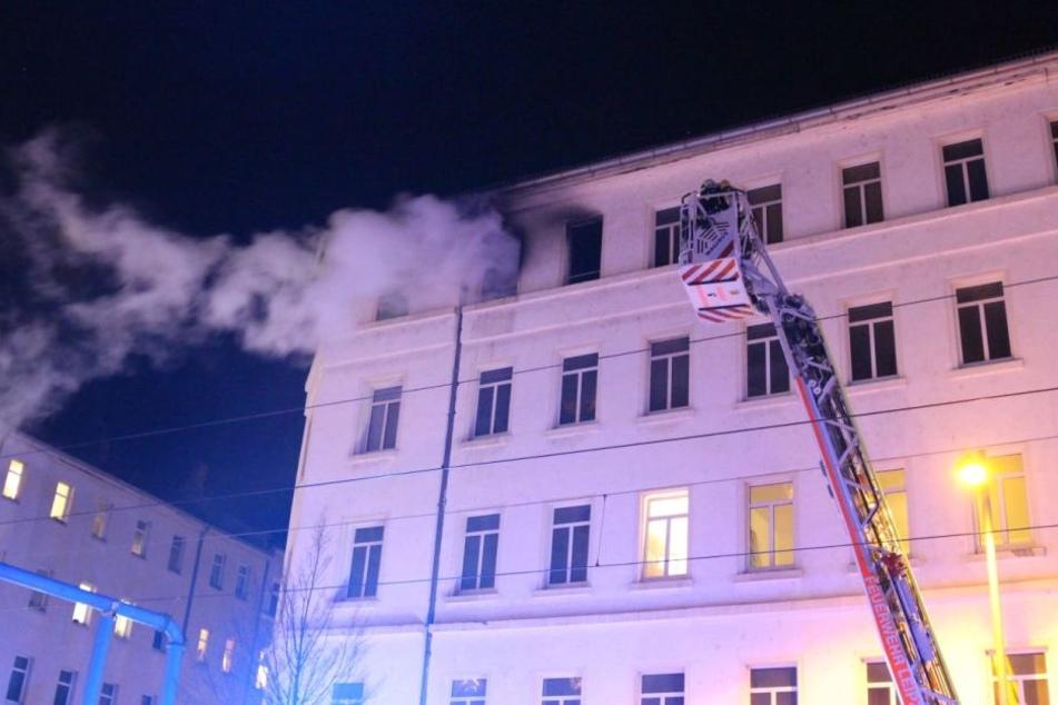 Kameraden der Leipziger Feuerwehr werden mit einer Drehleiter an der Fassade des Mehrfamilienhauses in die vierte Etage gefahren. Dort ist am Mittwoch ein Brand ausgebrochen.