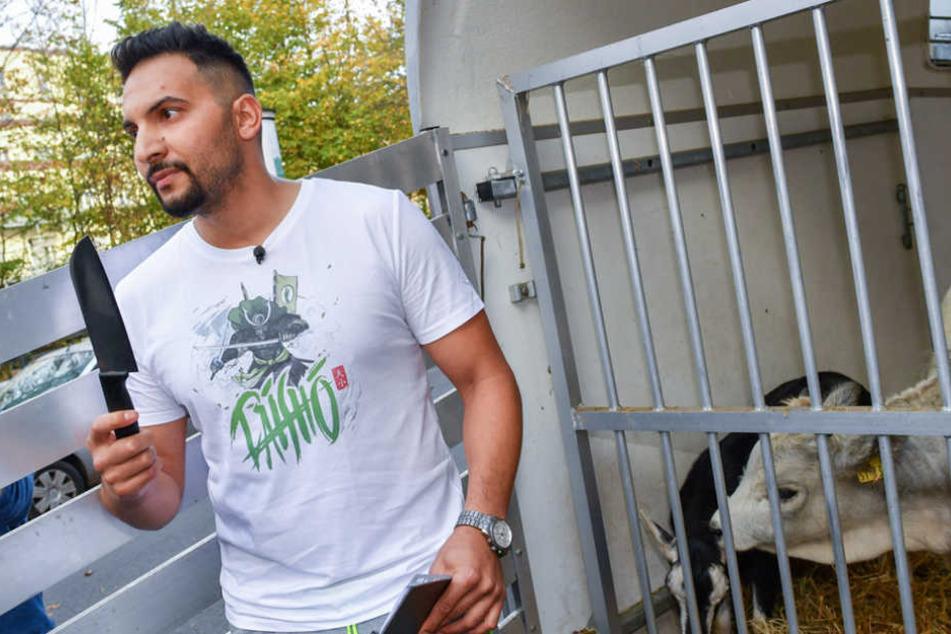 Der vegane Koch und TV-Promi Attila Hildmann steht in Berlin bei einem Pressetermin vor seinem veganen Imbiss mit einem Messer an einem Tiergatter.