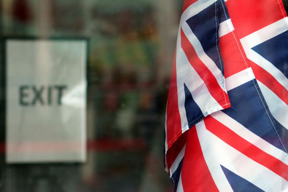 """Fahnen des Vereinigten Königreich Großbritannien hängen in London in einem Geschäft vor einem Schild mit der Aufschrift """"Exit""""."""