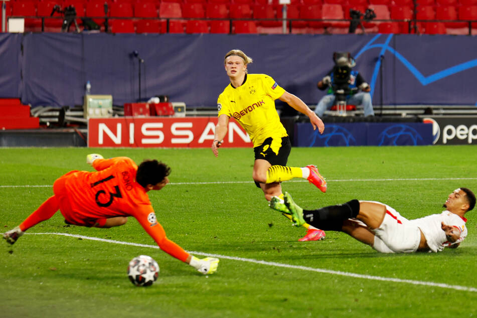 Der krönende Abschluss einer fantastischen ersten BVB-Hälfte: Erling Haaland (M.) überwindet Sevilla-Keeper Bono (l.) mit diesem Flachschuss in die linke Ecke zum 3:1 für Dortmund.