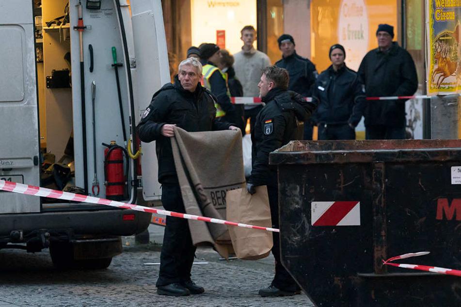 Polizisten bringen den Umschlag aus der Bank.