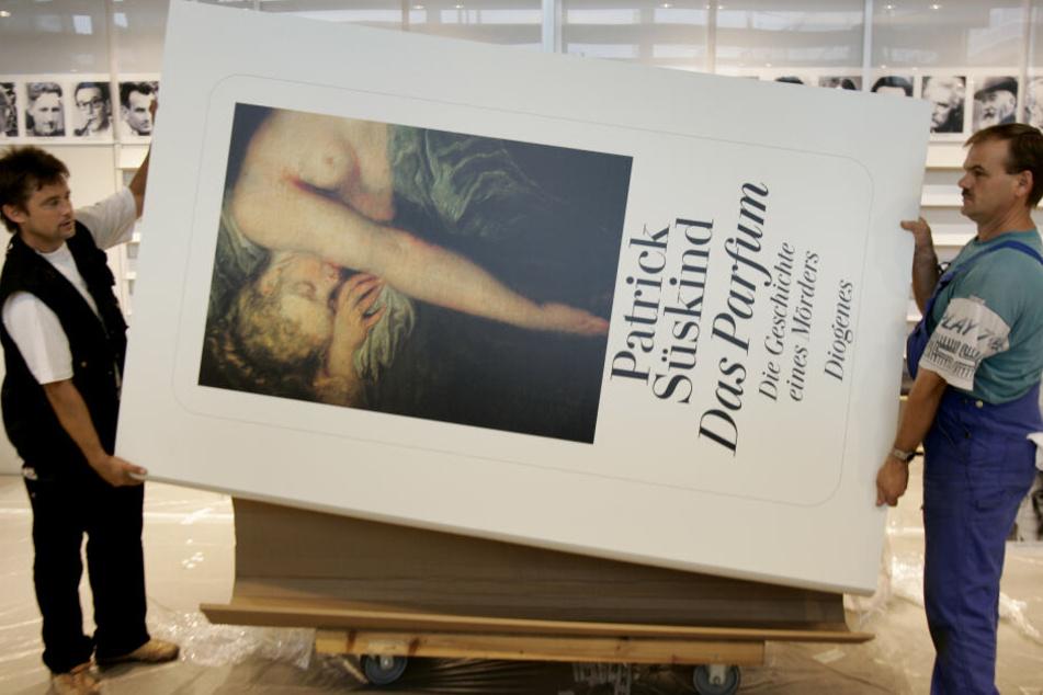 """Zwei Monteure tragen auf einem Messegelände das überdimensionale Buch """"Das Parfüm"""" von Patrick Süskind durch eine Halle. (Archivbild)"""