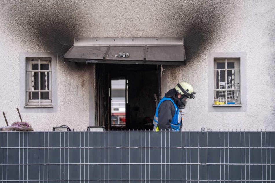 Ein Feuerwehrmann mit Atemschutz-Ausrüstung verlässt das Haus, in dem fünf Menschen bei einem Brand ums Leben kamen.