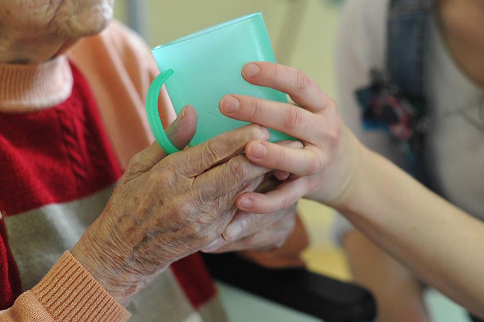 Eine Pflegekraft hilft einer alten Frau beim Trinken.