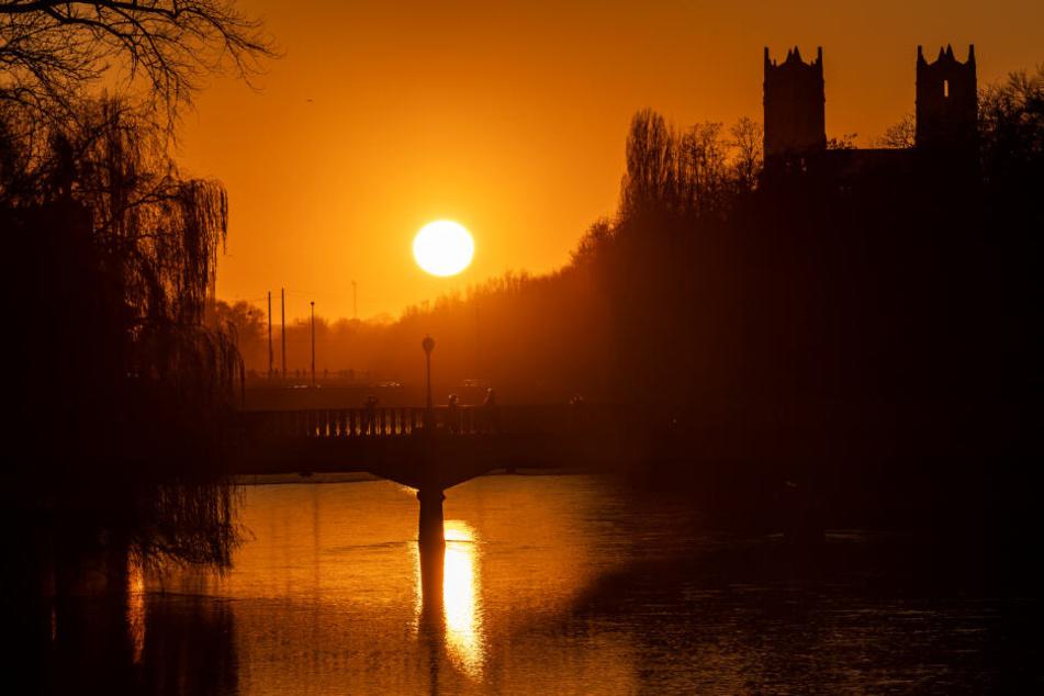 Die Sonne geht über der Isar unter, die von der Boschbrücke (von vorne nach hinten), der Corneliusbrücke und der Reichenbachbrücke überspannt wird.