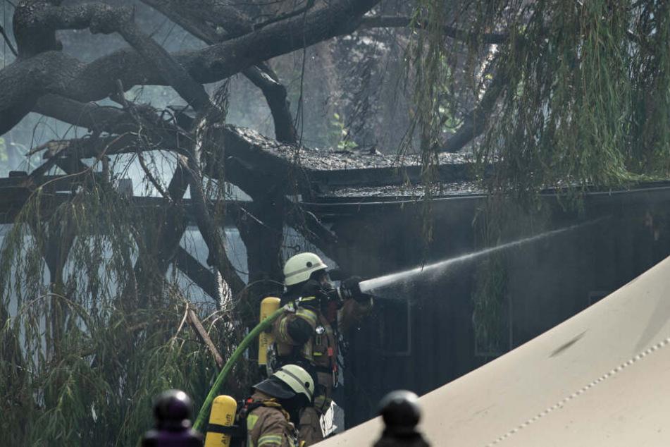 Feuerwehrleute bekämpfen auf einem Grundstück an der Straße Am Flutgraben einen Brand.