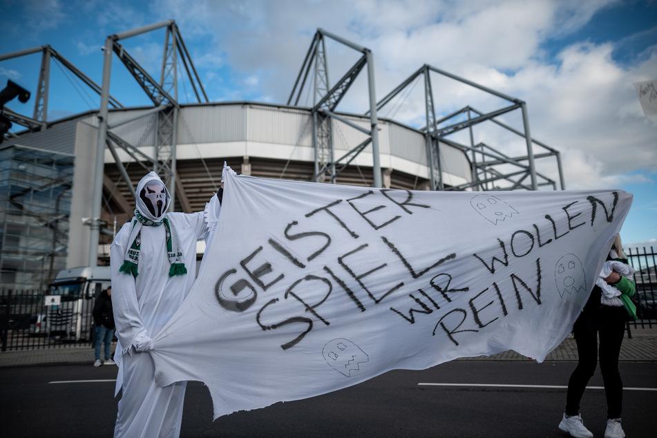 """Fans in Geisterkostümen stehen am 11. März vor dem Stadion in Mönchengladbach mit einem Banner auf dem """"Geisterspiel Wir wollen rein"""" steht."""
