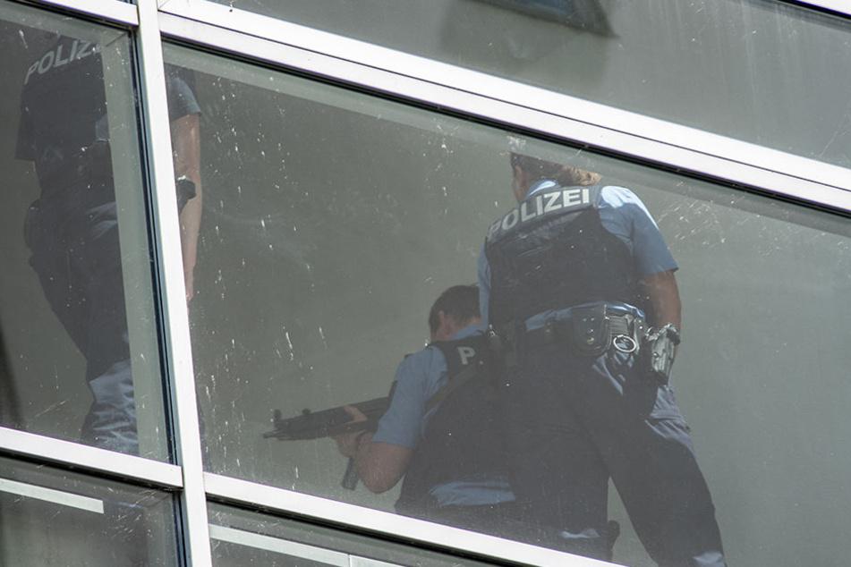 Schwer bewaffnete Polizisten nähern sich der nächsten Parkebene um diese abzusuchen.