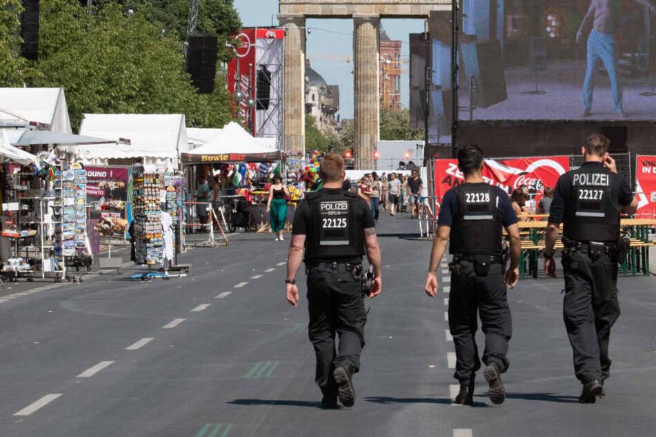 Polizisten gehen über die gesperrte Straße des 17. Juni, während nur wenige Fans die Übertragung des Achtelfinalspiels bei der Fußball-Weltmeisterschaft zwischen Schweden und der Schweiz verfolgen.