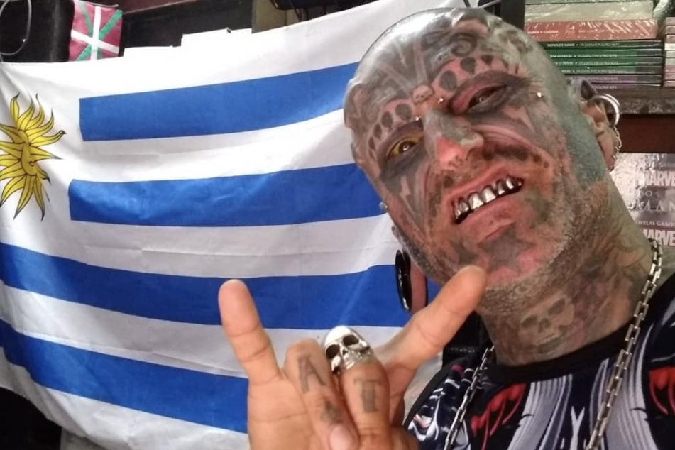 Victor Hugo Peralta Rodriguez flaunts his metal teeth in front of a Uruguayan flag.
