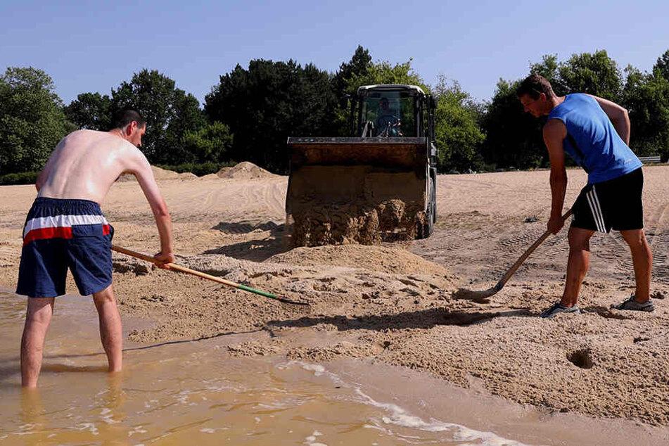 Fleißig verteilen die Männer den Sand im Strandbad - FKK gilt für sie aber nicht.