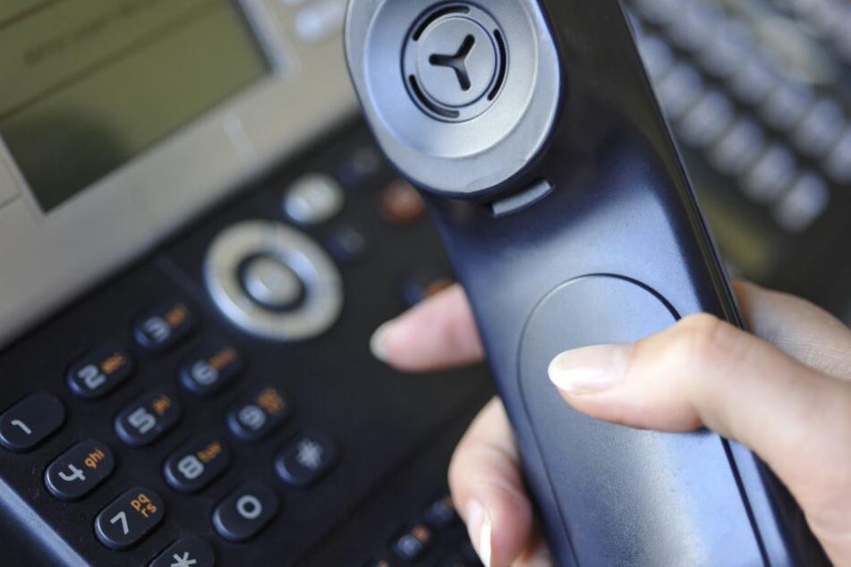 Eine Frau hält einen Telefonhörer in der Hand (Symbolbild).