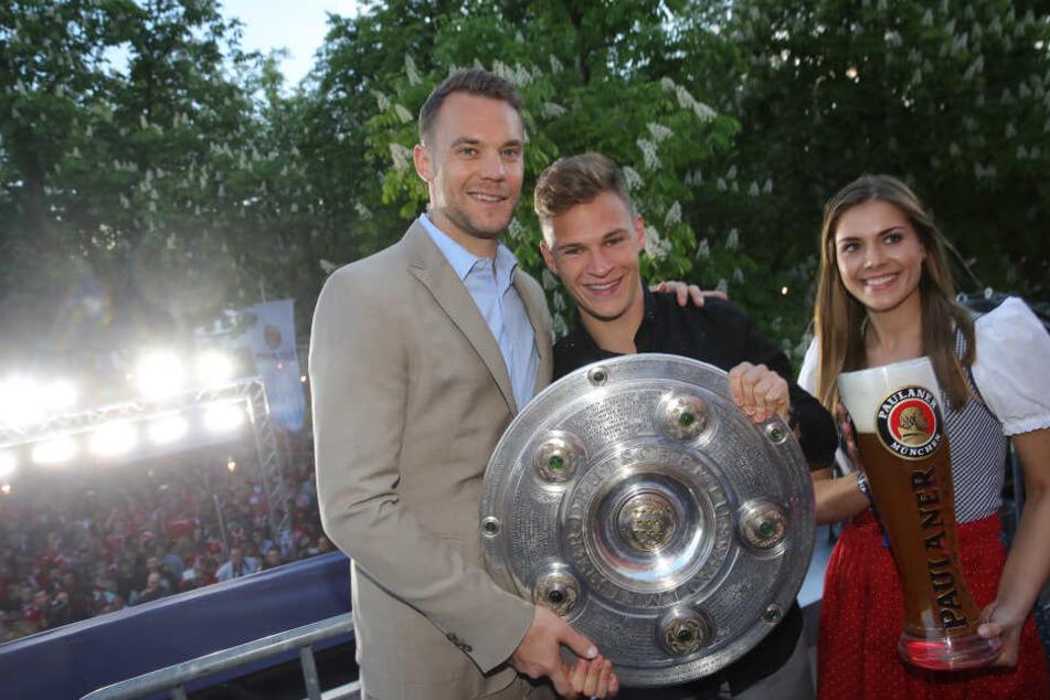 Manuel Neuer (l) von Bayern München und Joshua Kimmich stehen mit der Meisterschale bei einer Klub-internen Meisterfeier am Nockerberg.