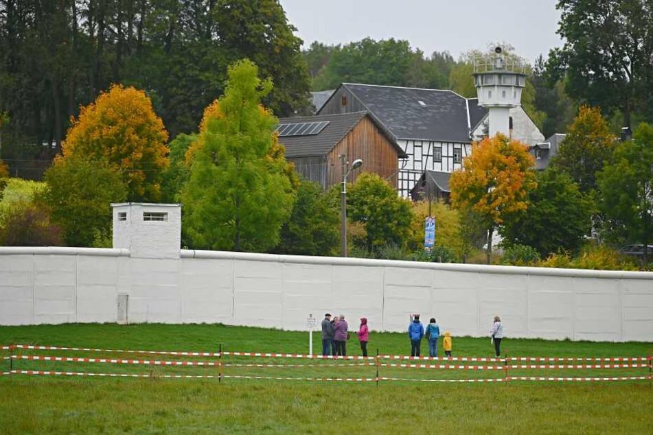 Besucher stehen vor einem Teil der ehemaligen Mauer. Im ehemals geteilten Dorf Mödlareuth wurde am Donnertag eine Einheitsfeier abgehalten.