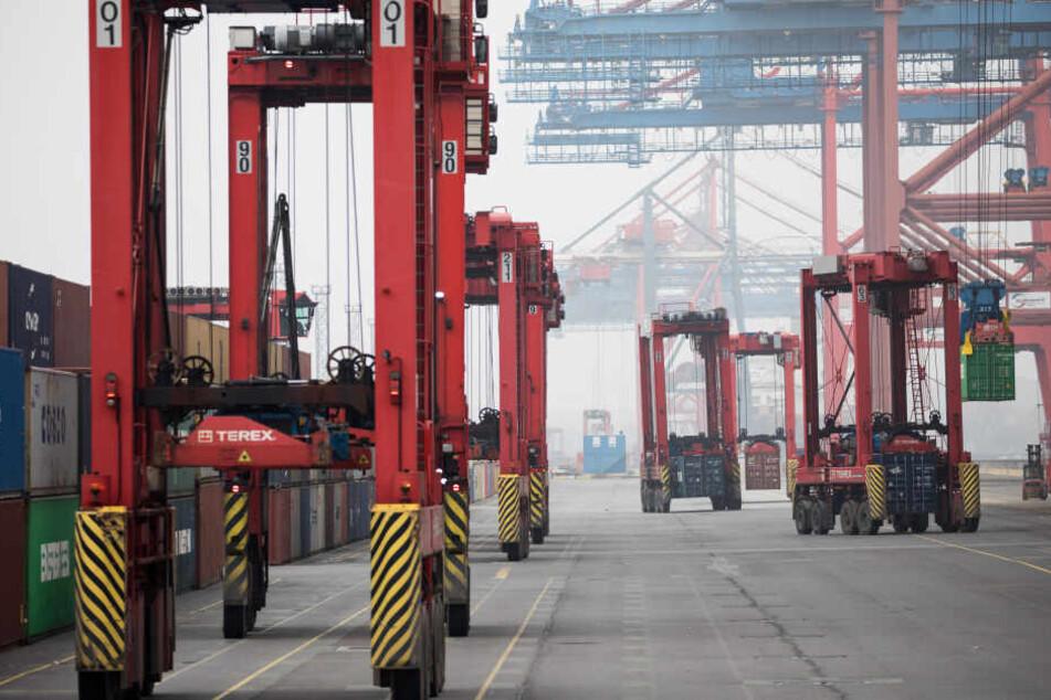"""Über 15 Meter hohe Portalhubwagen, die auch """"Van Carrier"""" genannt werden, sind bei der Be- und Entladung in einem Hamburger Terminal im Hafen unterwegs (Symbolbild)."""