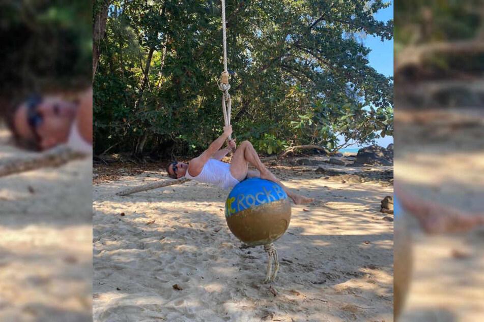 Musiker Sasha schwingt auf einer Kugel am thailändischen Strand.