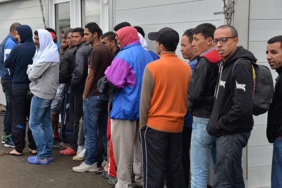 Bewohner der Außenstelle der Aufnahmeeinrichtung für Asylsuchende warten auf Kleider an der Ausgabe.