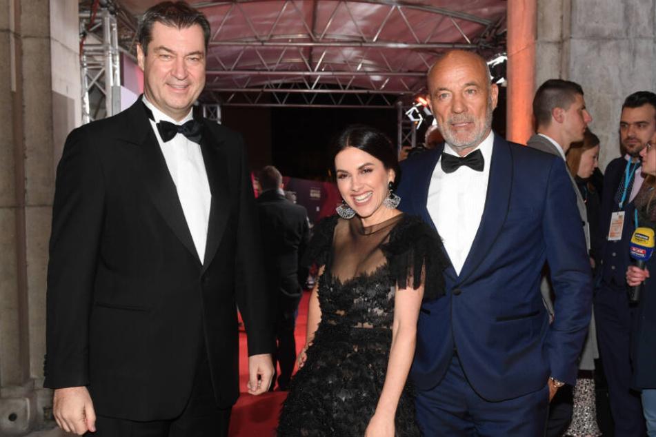 Bayerns Ministerpräsident Markus Söder (CSU, l), der Schauspieler Heiner Lauterbach und seine Frau, die Schauspielerin Viktoria Lauterbach.