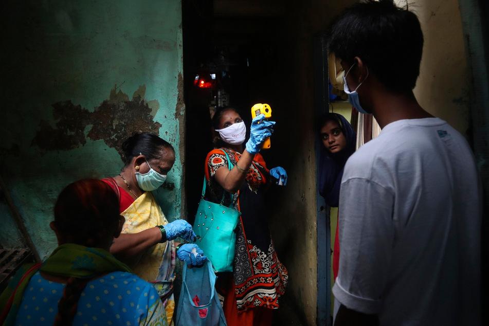 Eine Mitarbeiterin des Gesundheitswesens misst die Körpertemperatur von Bewohnern eines Slums.