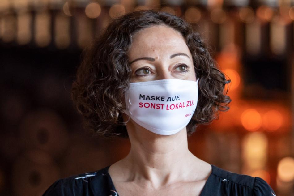 """Berliner Wirtschaftssenatorin, trägt bei einer Pressekonferenz zu einer Kampagne der Wirtschaftssenatsverwaltung und von visitBerlin zur Sensibilisierung für Corona-Regeln in Gaststätten eine Maske mit der Aufschrift """"Maske auf. Sonst Lokal zu.""""."""