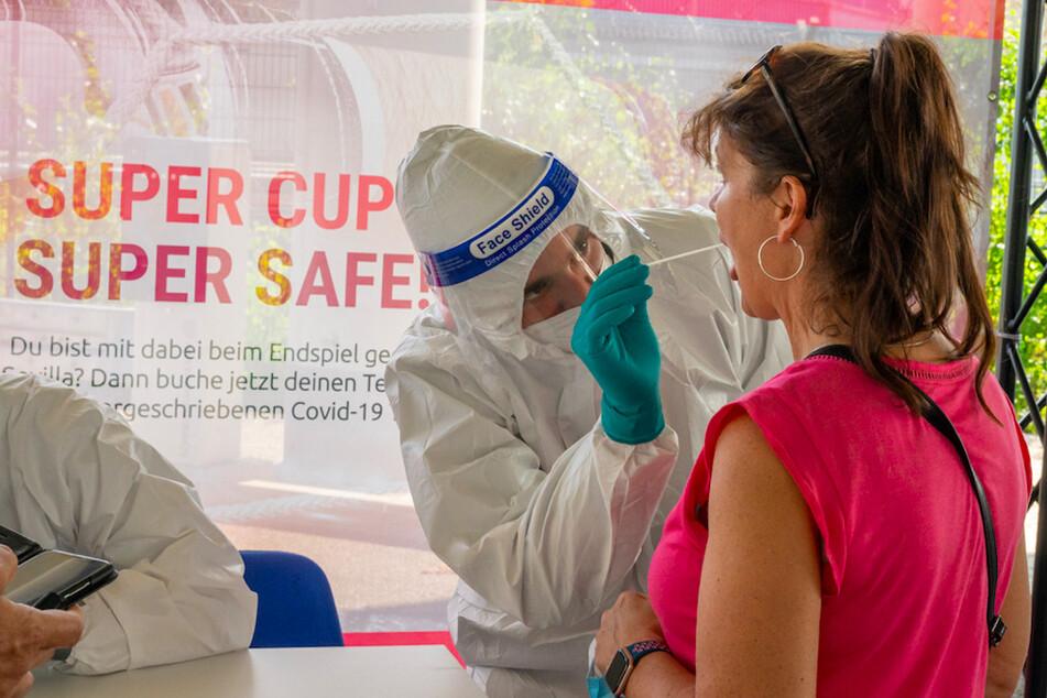 Ein Mann in Schutzanzug nimmt bei einem weiblichen FC Bayern Fan einen Corona-Test-Abstrich.