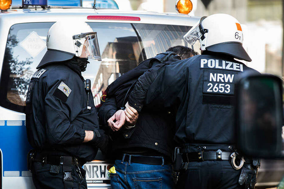 Polizisten führen in Düsseldorf einen randalierenden Demonstranten ab. Bei der Kurden-Demonstration ist es am Samstag zu Zusammenstößen mit der Polizei gekommen.