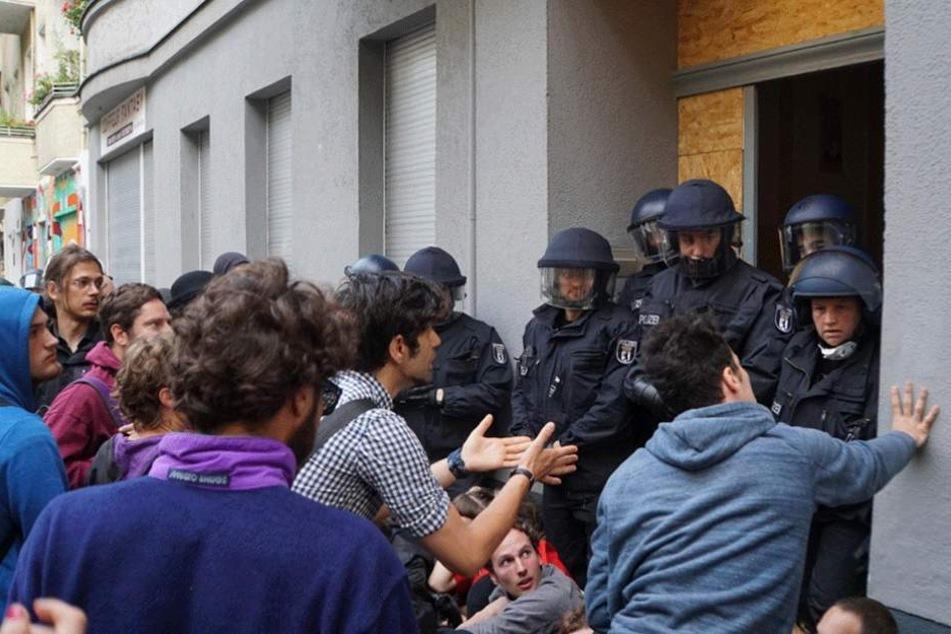 Demonstranten reden vor dem Friedel 54 auf die Polizisten ein.