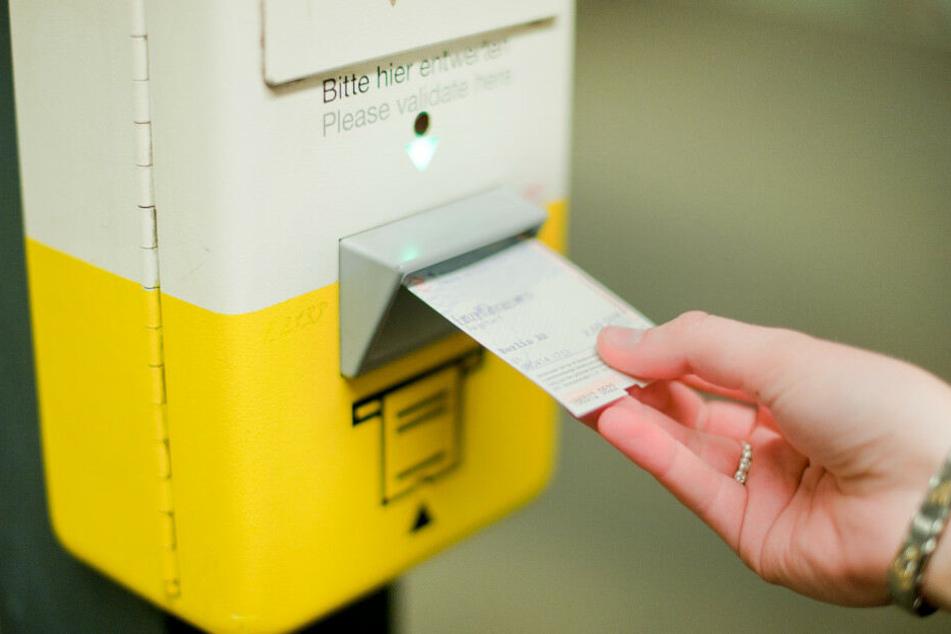Eine Frau entwertet an einem Fahrkartenentwerter der BVG in einem U-Bahnhof ihre Fahrkarte.