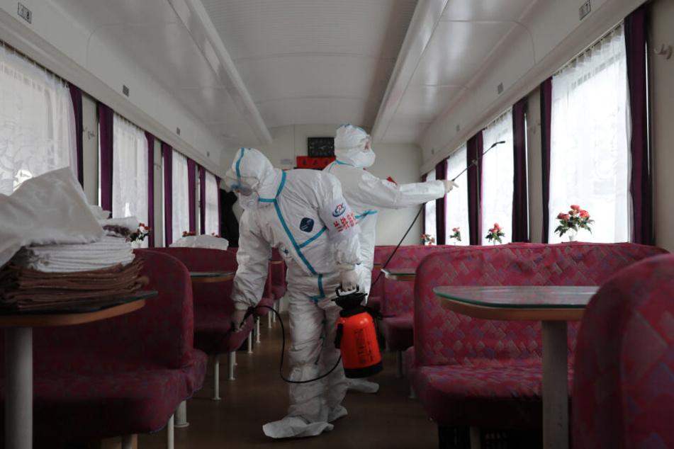 Arbeiter desinfizieren einen Zug.