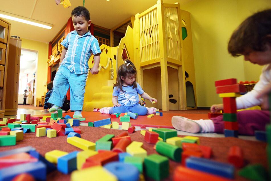 Kinder spielen mit bunten Bauklötzen in einer Kita.