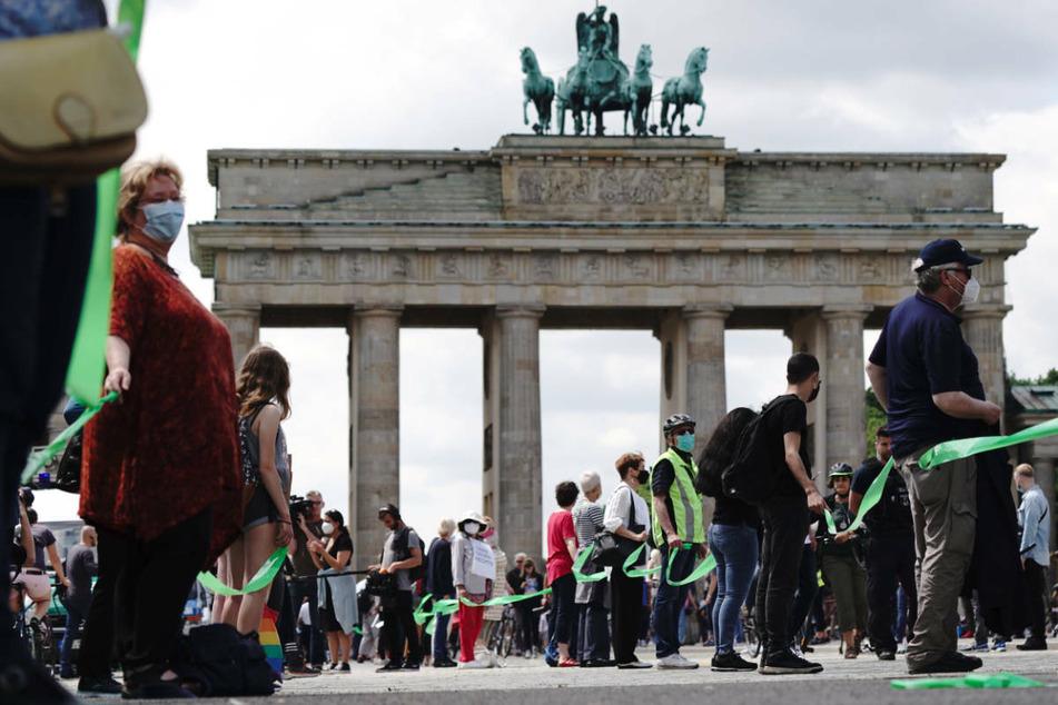 """Im Juni 2020 stehen Teilnehmer einer """"Unteilbar""""-Demonstration vor dem Brandenburger Tor. Am Samstag werden bis zu 30.000 Menschen bei einer weiteren Protestkundgebung des Bündnisses in Berlin erwartet."""