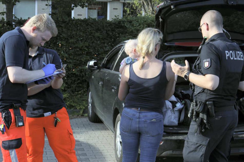 Ein Polizeibeamter spricht mit der Mutter, die ihr Kind wieder in den Armen halten kann.