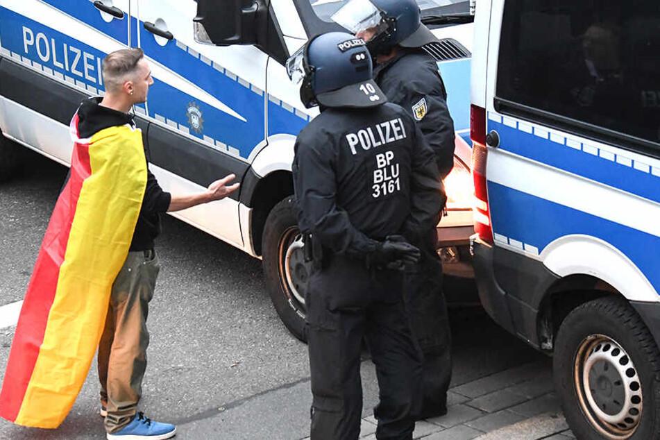 Ein Trauermarsch-Teilnehmer lässt sich auf eine Diskussion mit (den) Polizisten ein.