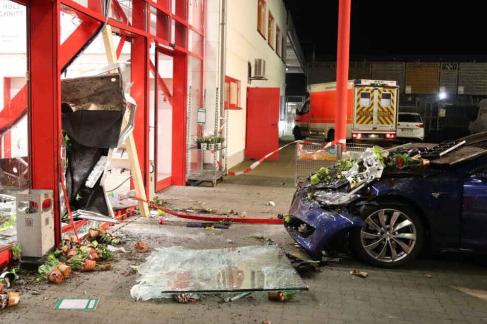 Nach dem Unfall steht der stark beschädigte Tesla vor den Trümmern der Fassade des Baumarktes in Nortorf.