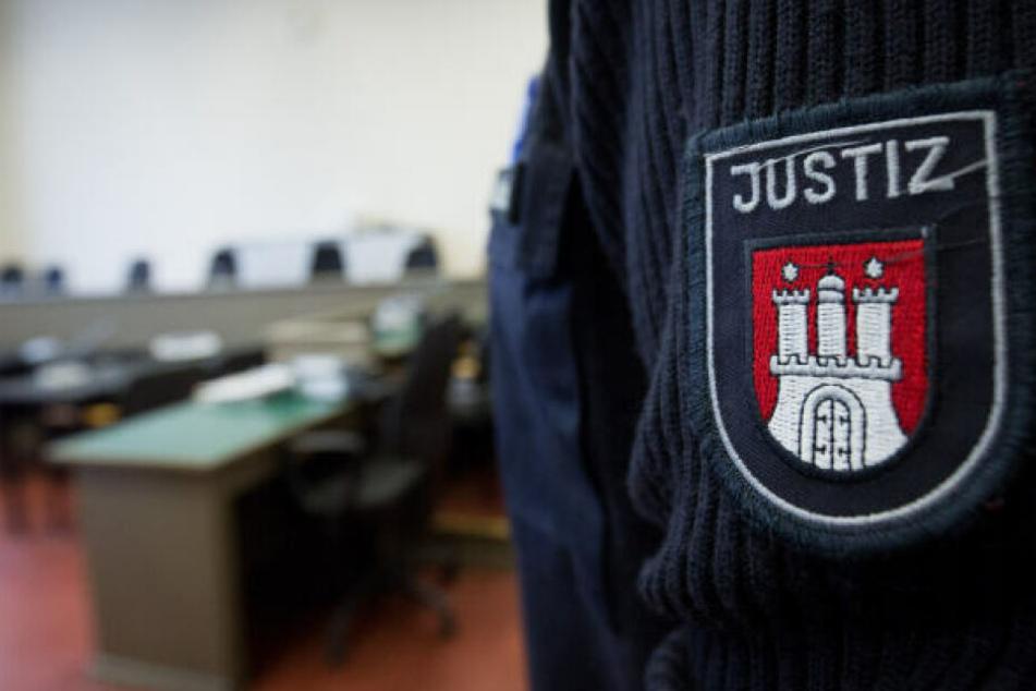 Ein Hamburger Justizbeamter steht vor einer Verhandlung im Gerichtssaal.