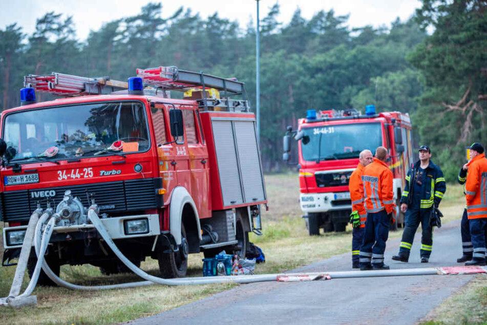 Feuerwehrleute warten bei Hohen Woos am Rand des brennenden Waldgebiet.