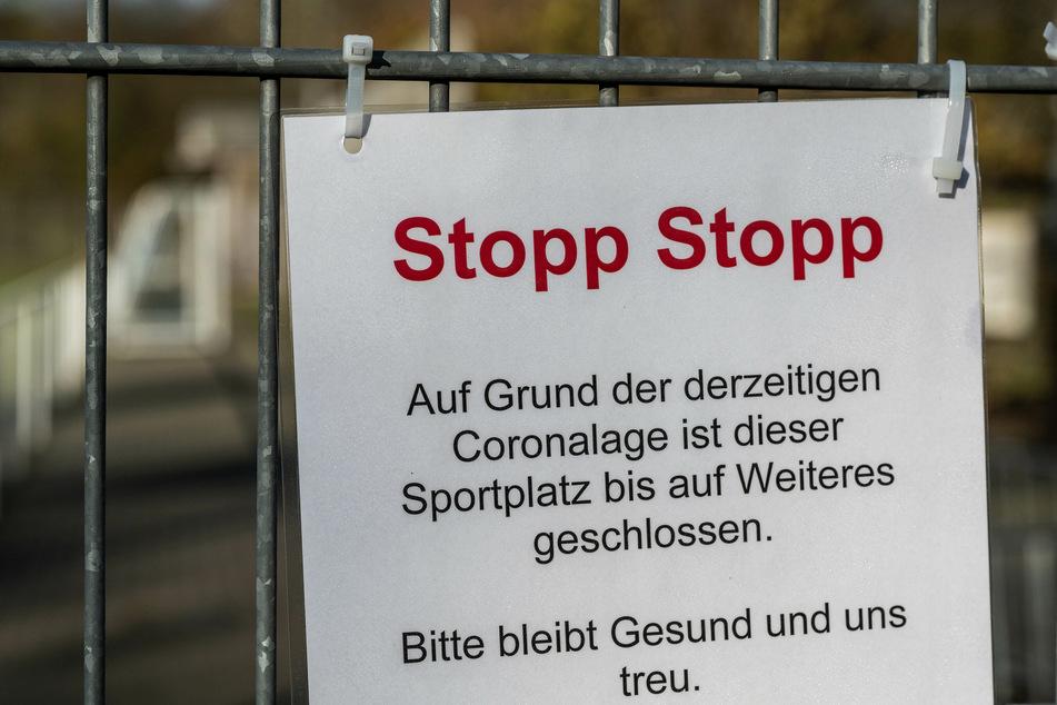 Ein Schild hängt am Zaun eines Fußballplatzes.