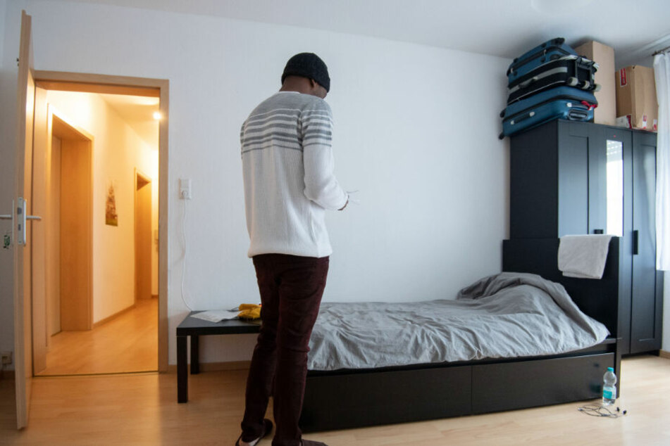 Ein Bewohner einer Männerschutzwohnung betrachtet in seinem Zimmer Unterlagen.