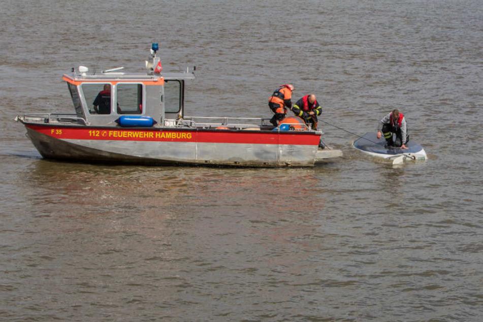 Die Feuerwehr rettete den Skipper aus der Elbe, der noch auf seiner Jolle hockte.