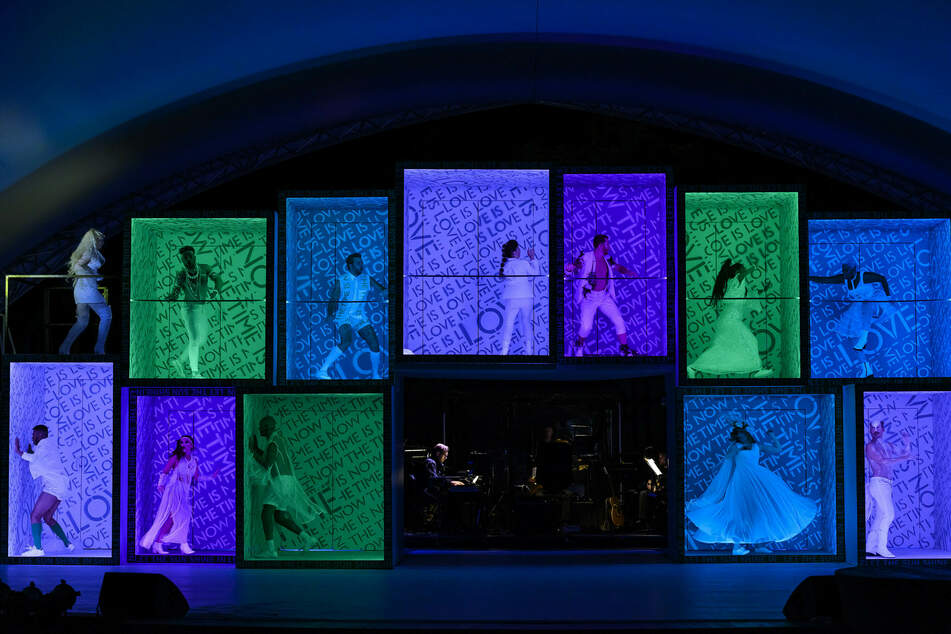 Das Bühnenbild besteht aus einer Wand mit Boxen, die den Darstellern helfen den Abstand zu wahren.