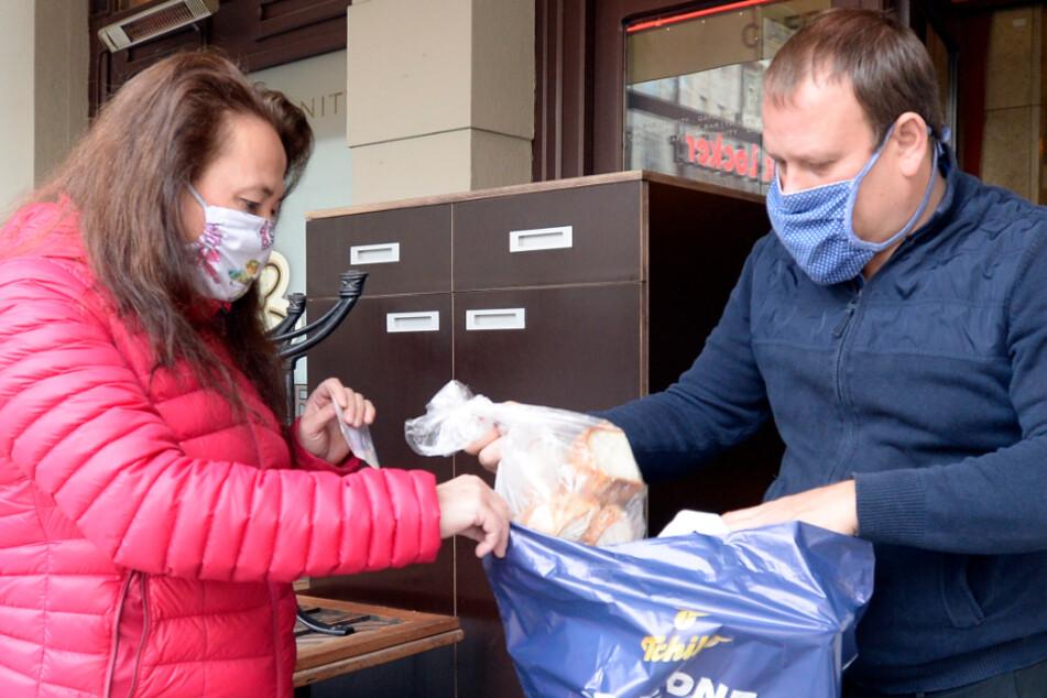 Eine Kundin nimmt Essen aus einem Restaurant entgegen, welches seinen Gastbetrieb vorübergehend aufgrund der Corona-Pandemie eingestellt hat.