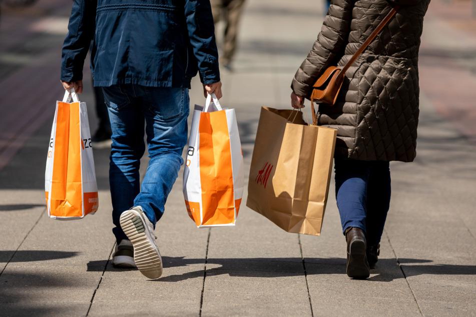 Passanten halten Einkaufstüten in den Händen. Wegen sinkenden Infektionszahlen kann in einigen Städten, nach vorheriger Terminvereinbarung, wieder geshoppt werden. (Symbolbild)