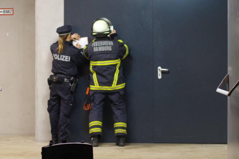 Eine Polizisten und ein Feuerwehrmann machen an einer Tür Notizen.