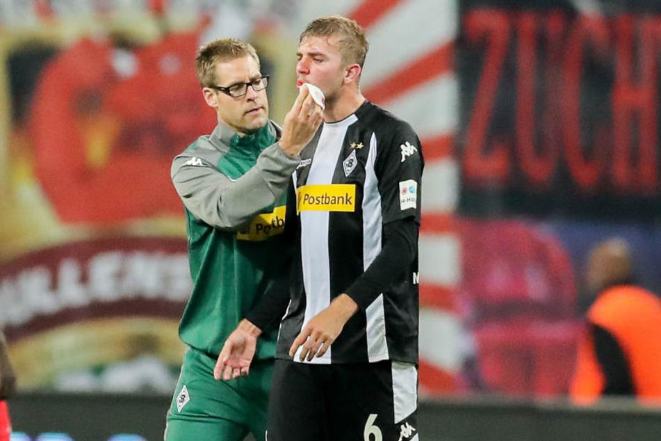 Sichtlich mitgenommen wird Christoph Kramer von einem Teamarzt versorgt. Keita hatte den Gladbacher mit seinen Stollen im Gesicht getroffen.