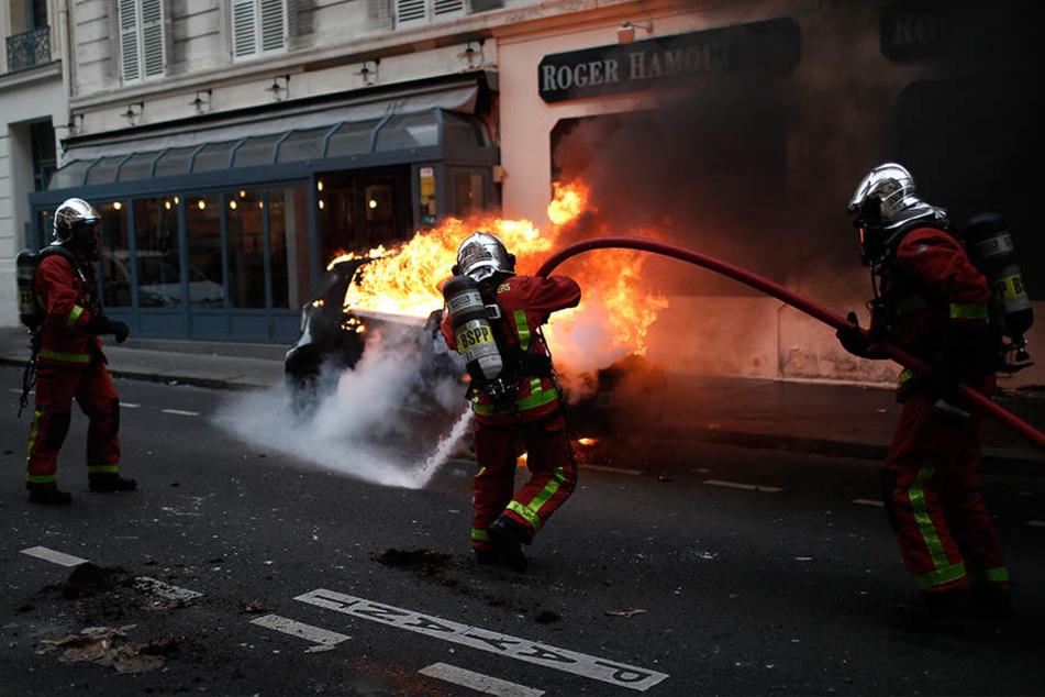 """Feuerwehrleute löschen während der Proteste und Ausschreitungen der """"Gelbwesten"""" in Paris ein brennendes Auto."""