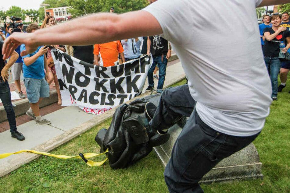 Ein Demonstrant tritt nach einem am Boden liegenden Denkmal eines konföderierten Soldaten.